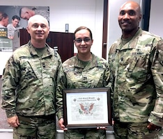 Capt. Rosita Fregoso (center), commander of Company D, 232nd Medical Battalion, accepts a certificate of appreciation for being the guest speaker at the Lesbian, Gay, Bisexual, Transgender, or LGBT, Pride Month Observance June 30, from Col. Clinton W. Schreckhise (left), 32nd Medical Brigade commander, and Command Sgt. Maj. Thomas Oates (right).