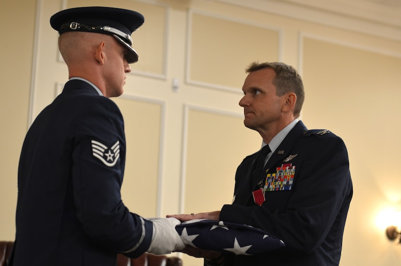 U.S. Air Force Col. Dustin P. Smith,right, Headquarters U.S. Air Forces Central Command chief of staff, receives a flag from the Team Shaw Honor Guard during his retirement ceremony, July 14, 2017, Shaw Air Force Base, S.C. Smith was a senior air battle manager with 1,800 flight hours in the NATO E-3A and E-3 B/C aircraft. (U.S. Air Force photo by Senior Airman Christopher Maldonado)