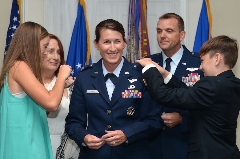 U.S. Air Force Col. Kristine B. Smith, 710th Combat Operations Squadron deputy director from Joint Base Langley-Eustis, Va., stands surrounded by her family as they pin on her colonel rank, July 14, 2017, Shaw Air Force Base, S.C. Smith was promoted by Col. Dustin P. Smith, Headquarters U.S. Air Forces Central Command chief of staff and her husband, as his last official duty in the Air Force. (U.S. Air Force photo by Senior Airman Christopher Maldonado)