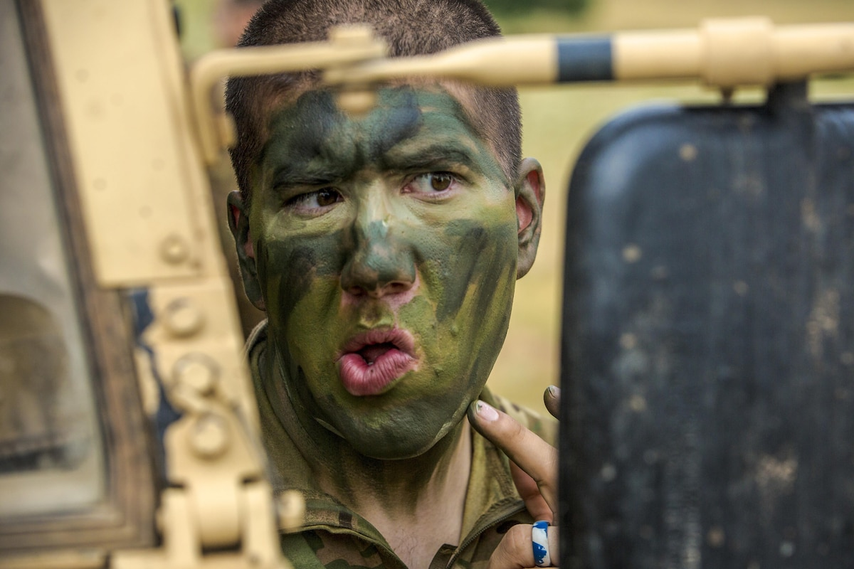A soldier applies face paint using a vehicle's mirror.