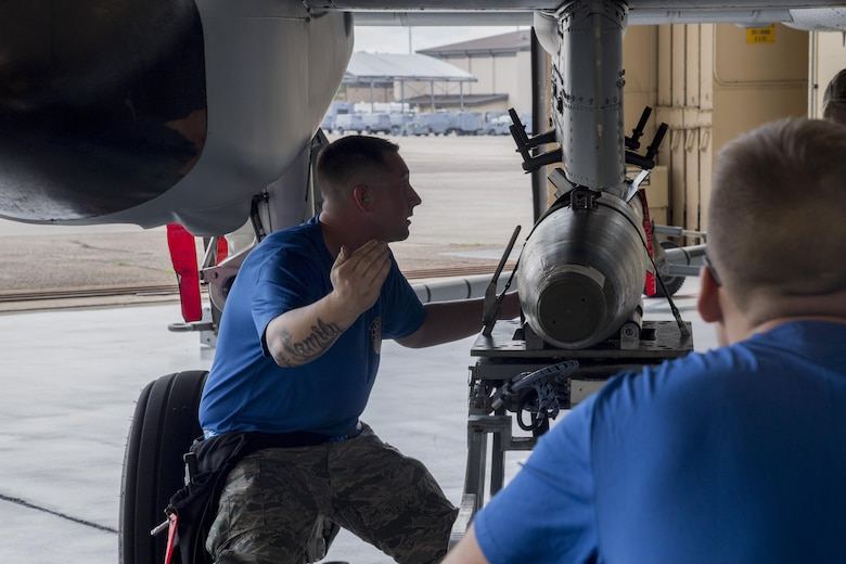 Staff Sgt. Johnathan Grieg, 74th Aircraft Maintenance Unit weapons load team chief, guides a GBU-12 joint direct attack munition to load onto an A-10C Thunderbolt II during a weapons load competition July 14, 2017, at Moody Air Force Base, Ga. Every quarter members of the 74th and 75th AMU competes in the quarterly competition that tests knowledge, dress and appearance, and speed of loading a GBU-12 joint direct attack munition and AIM-9 Sidewinder. (U.S. Air Force photo by Staff Sgt. Eric Summers Jr.)