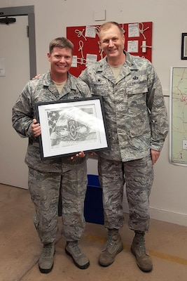 Col. Jonathan Wright, 502nd Installation Support Group commander, presents Tech. Sgt. Daniel Solon, 502nd Civil Engineer Squadron explosive ordnance disposal technician, a drawing of the EOD badge in appreciation for an outstanding mission briefing Solon delivered, Sept. 21 at Joint Base San Antonio-Lackland, Texas.