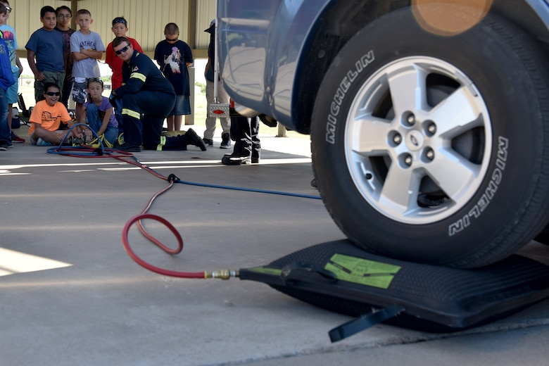 Jay Teague, 17th Civil Engineer Squadron firefighter, teaches Addalynn Krickland and Josilyn Teague, junior firefighters, how to use compressed air to lift a vehicle during the junior firefighter camp at the fire station on Goodfellow Air Force Base, Texas, July 11, 2017. During the weeklong course, the children learned how to use fire extinguishers, tie a variety of knots and how to safely climb and descend a ladder. (U.S. Air Force photo by Staff Sgt. Joshua Edwards/Released)