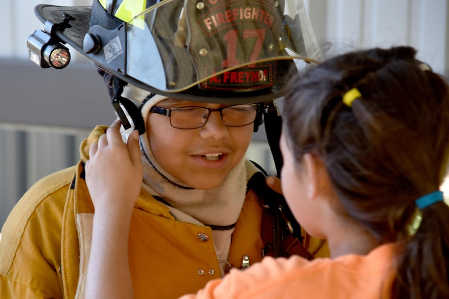 Addalynn Krickland, junior firefighter, helps Karah Teague, junior firefighter, put on a fire helmet during the junior firefighter camp at the fire station on Goodfellow Air Force Base, Texas, July 11, 2017. Krickland raced against another child to see if they could get dressed as quickly as a firefighter. (U.S. Air Force photo by Staff Sgt. Joshua Edwards/Released)
