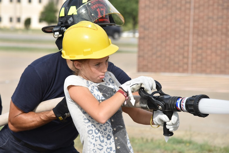 Josilyn Teague, junior firefighter, sprays a fire hose during the junior firefighter camp at the fire station on Goodfellow Air Force Base, Texas, July 13, 2017. Teague practiced shooting a basketball to test her aim. (U.S. Air Force photo by Staff Sgt. Joshua Edwards/Released)