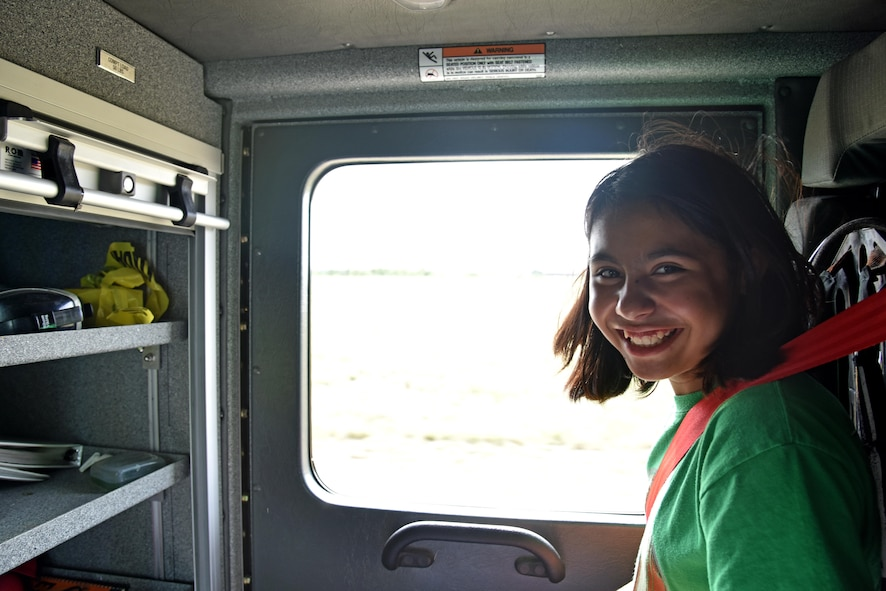 Alexa Fadilla, junior firefighter, rides in a firetruck during the junior firefighter camp at the fire station on Goodfellow Air Force Base, Texas, July 13, 2017. The firefighters taught the children a variety of skills during the camp including the importance of staying low during a fire and first aid tips. (U.S. Air Force photo by Staff Sgt. Joshua Edwards/Released)