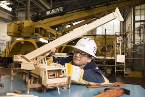Jeff Iller, a Code 722 crane inspector, shows off a wood crane he made of walnut and maple that resembles a GMK mobile hydraulic extendable boom crane. The two-foot long crane has a boom which extends to 52 inches.