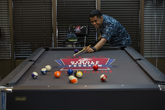 U.S. Navy Seaman Miguel Prima, a preventative medicine technician at the Robert M. Casey Medical and Dental Clinic, plays pool at the Single Marine Program's Marine Lounge grand opening at Marine Corps Air Station Iwakuni, Japan, July 14, 2017. Originally located on the second floor over Crossroads Mall, the Marine Lounge was moved to make it more available to single and unaccompanied service members on the air station. The lounge provides tablets for service members to check out. The new movie room offers a better experience because of new recliners, an 86-inch television and a brand new surround sound speaker system. (U.S. Marine Corps photo by Lance Cpl. Gabriela Garcia-Herrera)