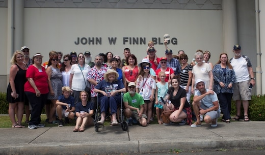 MARINE CORPS BASE HAWAII - The family of John Finn poses for a photo in front of the John Finn Memorial Building at the end of their tour aboard Marine Corps Base Hawaii, July 14, 2017. The tour allowed family members to explore the legacy left by Finn after carrying out the feats of heroism that earned himself the first Medal of Honor of WWII. (U.S. Marine Corps Photo by Lance Cpl. Luke Kuennen)