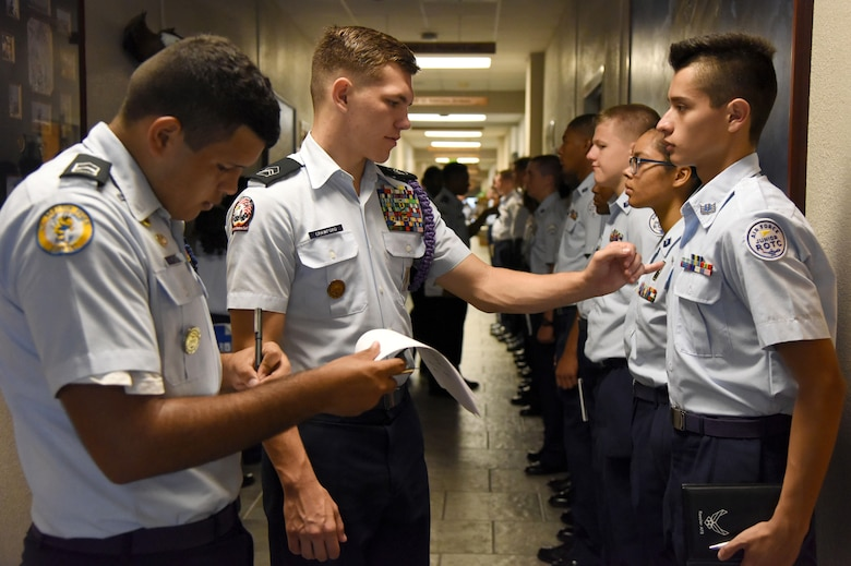 Mississippi Air Force Junior ROTC cadets Natanael Rivera, St. Martin High School, and Kane Crawford, Bay High School, Bay St. Louis, conduct a uniform inspection on Jose Martinez, Biloxi High School, during a JROTC Cadet Leadership Course at the Mathies NCO Academy July 12, 2017, on Keesler Air Force Base, Miss. Approximately 140 JROTC students from 15 high schools in five states attended the week-long course at Keesler that ended with a parade and graduation ceremony. (U.S. Air Force photo by Kemberly Groue)