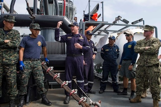 CALLAO, Peru (July 17, 2017) Captain Carlo Mario Bertalmio, commandant of the Peruvian vessel BAP Morales (RAS-180), center, gives a safety briefing to Peruvian and American Sailors before conducting a joint diving and salvage training exercise during UNITAS 2017. UNITAS is an annual, multi-national exercise that focuses on strengthening our existing regional partnerships and encourages establishing new relationships through the exchange of maritime mission-focused knowledge and expertise during multinational training operations. (U.S. Navy photo by Mass Communication Specialist 2nd Class Bill Dodge/Released)