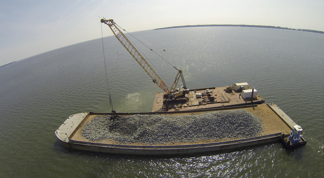 Granite rock, which is brought in by barge, is methodically placed in the Piankatank River near Gwynn's Island in Mathews County Virginia. The rock is the basis for the newest, 25-acre oyster reef in the Chesapeake Bay Watershed. The Norfolk District, U.S. Army Corps of Engineers, is overseeing the more than $2 million sanctuary reef project in partnership with the Virginia Marine Resources Commission and the Nature Conservancy.   (U.S. Army photo/Patrick Bloodgood)