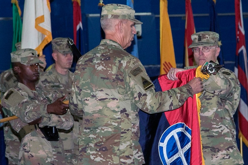 Maj. Gen. Victor J. Braden, commanding general of the 35th Infantry Division, and Command Sgt. Maj. Timothy Newton, senior enlisted advisor, uncase the division's colors during the Task Force Spartan transfer of authority ceremony, at Camp Arifjan, Kuwait, July 13, 2017. The 35th Infantry Division assumed command of TF Spartan, part of Operation Spartan Shield, from the 29th Infantry Division. TF Spartan highlights the vital role played by Army National Guard and Army Reserve Soldiers in operations around the world.