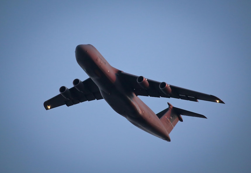 A U.S. Air Force C-5 Galaxy from the 436th Airlift Wing flies over New Jersey while lit by the setting sun. The C-5, one of the largest military aircraft, provides the Air Force with heavy intercontinental strategic airlift capability. The 436th Airlift Wing is located at Dover Air Force Base, Del. (U.S. Air National Guard photo by Tech. Sgt. Matt Hecht/Released)