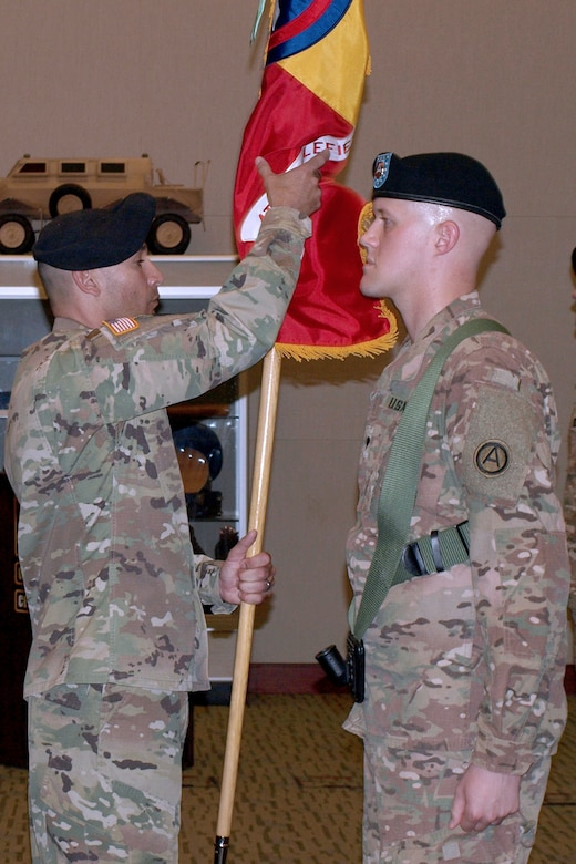 Command Sgt. Maj. Miguel Quiros, center, from the 4th Battlefield Coordination Detachment, U.S. Army Central, takes the 4th BCD's colors from Spc. Adam Burkett during the 4th BCD's change of command ceremony at Patton Hall on Shaw Air Force Base, S.C., July 11, 2017. Col. Samuel Saine, 4th BCD outgoing commander, relinquished his command of the detachment to Col. Geoffrey Adams, 4th BCD incoming commander.
