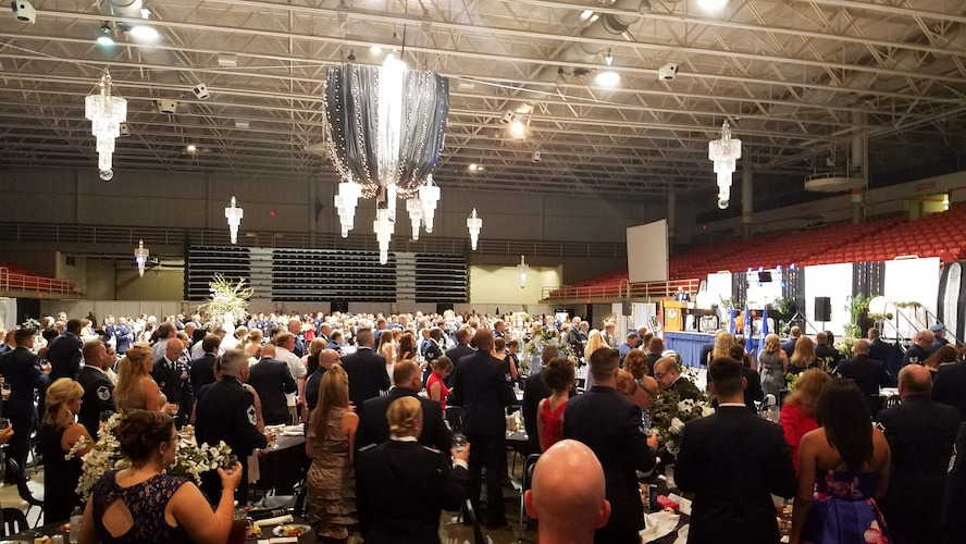 """Airmen assigned to the Missouri Air National Guard's 139th Airlift Wing stand for a moment of silence during the wing's military ball in St. Joseph, Mo., July 8, 2017. The ball was held at the Civic Arena and the theme was 'eclipse the night."""" (U.S. Air National Guard photo by Master Sgt. Michael Crane)"""