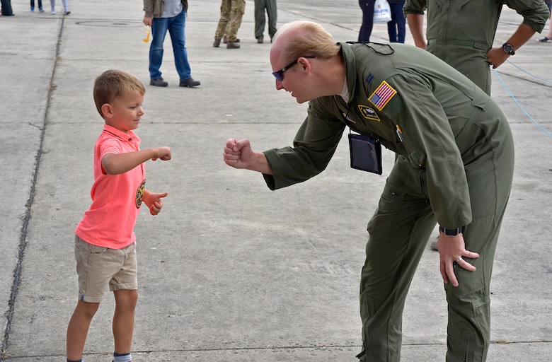 Capt. Michael Hart fist-bumps a young child at the Royal International Air Tattoo in Fairford, U.K.  A crew from the 315th Airlift Wing participated in the three-day airshow.  The airshow celebrated the 70th anniversary of the U.S. Air Force. (U.S. Air Force Photo by Maj. Wayne Capps)
