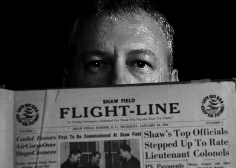 Christopher Koonce, 20th Fighter Wing historian, holds a 1942 edition of the Shaw Field Flight-Line newspaper at Shaw Air Force Base, S.C., July 12, 2017. As the wing historian, Koonce documents the ever-changing warfighter environment, at home and while deployed, by gathering data in historical documents, writing in archives and sharing knowledge with others. (U.S. Air Force photo illustration by Airman 1st Class Kathryn R.C. Reaves)