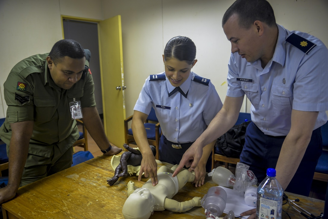 Republic of Fiji Military Forces Sgt. Natoga Anitelu, left, a medical services technician, discusses the best ways to clear an infant's airway with U.S. Air Force Capt. Paola Rosa, center, and U.S. Air Force Maj. Scott Stewart, right, during a subject-matter expert exchange (SMEE) at a health care center in Ba, Fiji, July 11, 2017. These SMEE events afforded multilateral international participants and non-governmental organizations opportunities to share knowledge and improve each other's skillsets. The events kicked-off Pacific Angel 2017 in Fiji, which lasts until July 24, 2017. (U.S. Air Force photo/Capt. Samantha Morrison)