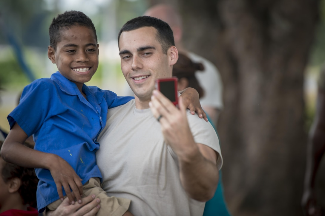 U.S. Air Force Senior Airman Benjamin Haase, a physical therapy assistant with the 673rd Medical Operations Squadron at Joint Base Elmendorf-Richardson, Alaska, takes a selfie with a Fijian boy during a sports day community engagement activity at the Lautoka School for Special Education in Lautoka, Fiji, July 14, 2017. The event afforded U.S. service members participating in Pacific Angel 2017 an opportunity to play with nearly 50 students in various field day-esque games designed to bring the two nations closer as allies and friends. (U.S. Air Force photo/Tech. Sgt. Benjamin W. Stratton)