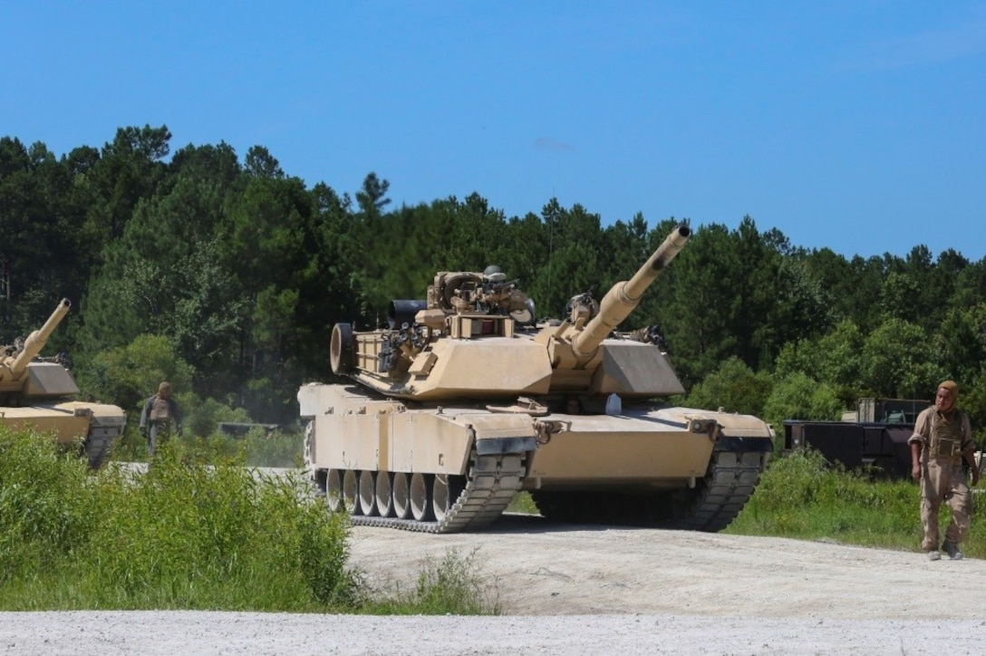 A Marine guides an M1A1 battle tank to its firing position during a combined arms range for Iron Wolf 17 at Camp Lejeune, N.C., July 14, 2017. Iron Wolf 17 is a multi-unit exercise designed to simulate battlefield conditions Marines may face while deployed. The tanks are from 2nd Tank Battalion, 2nd Marine Division. (United States Marine Corps photo by Cpl. Jon Sosner)