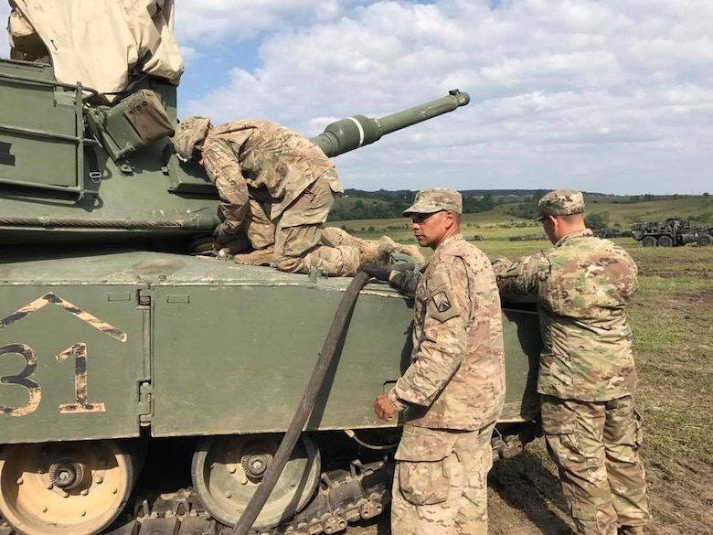 Sgt. Cruz Cotto, a motor transport operator with 515th Transportation Company, uses the retail fuel hose of the M969 5,000 gallon fuel tanker to refuel an M1 Abrams tank in Cincu, Romania on July 7.  (U.S. Army photo by 2nd Lt. Nnamdi Okangba)