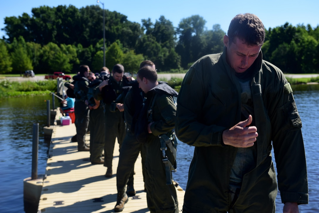 Staff Sgt. Joshua Krape, 4th Operations Support Squadron survival, evasion, resistance and escape specialist (right), pilots, and weapons systems officers from Seymour Johnson Air Force Base, North Carolina, prepare to start a water survival training course, June 28, 2017, at Buckhorn Reservoir, North Carolina. Pilots and WSO's are required to recertify their WST and combat survival training courses every three years. (U.S. Air Force photo by Airman 1st Class Kenneth Boyton)