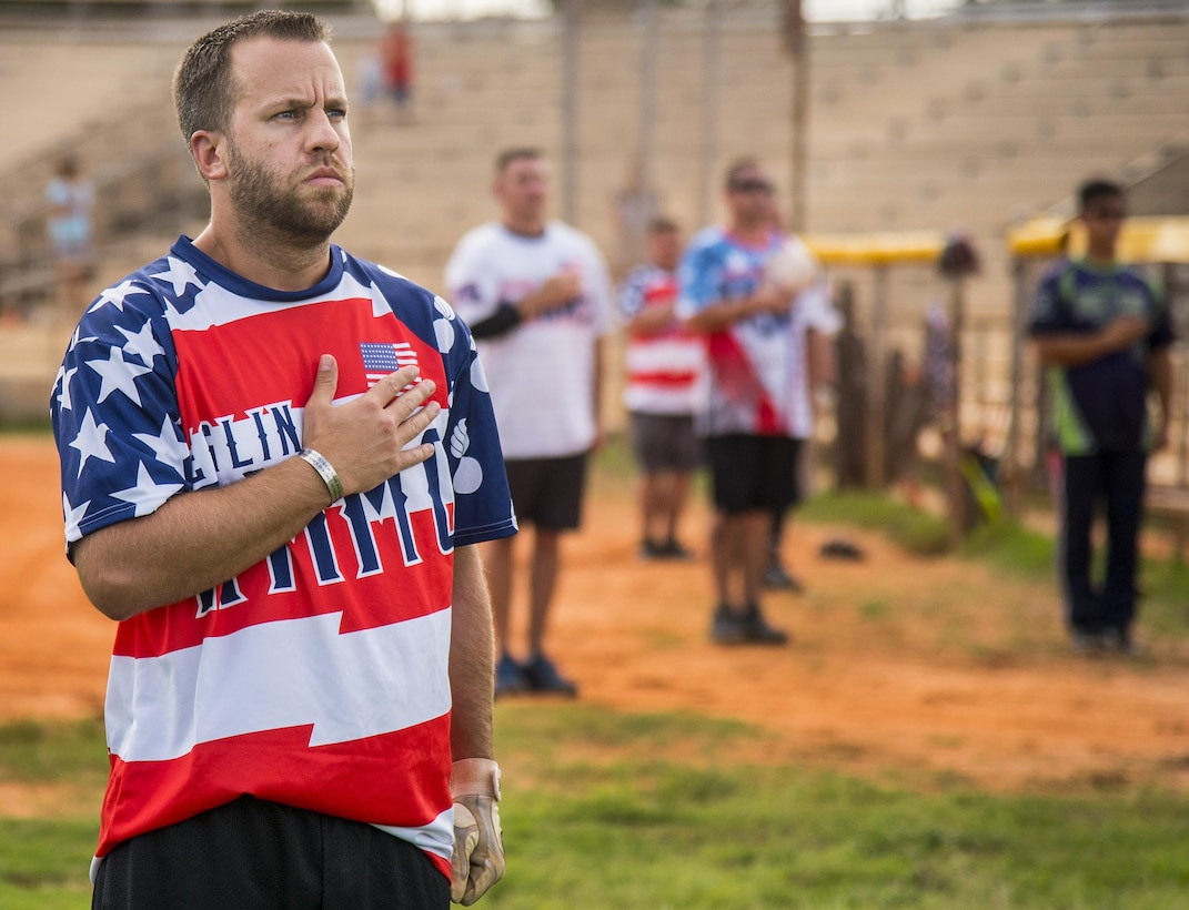 Kris Hampton, 96th Maintenance Squadron, stands with his hand over his heart during the National Anthem prior to his team's intramural softball game against the 359th Training Squadron team July 17 at Eglin Air Force Base, Fla.  The league-leading Maintainers pounded the training squadron 10-5 to improve to 9-1 on the season.  (U.S. Air Force photo/Samuel King Jr.)