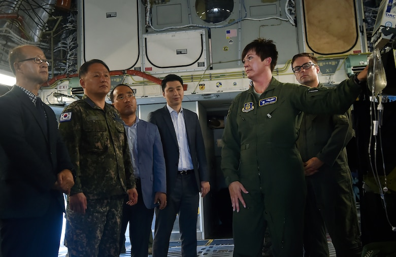 U.S. Air Force Capt. Charis Vincent, right, 315th Aeromedical Evacuation Squadron, briefs Col. Heon Jeong, center left, Republic of Korea Air Force Headquarters transportation branch chief, and ROK members of the U.S. Air Transportation Working Group, during a visit here July 13. The engagement was part of an annual meeting in support of the Mutual Airlift Support Agreement. U.S. - ROK ATWG members toured a C-17 Globemaster III and observed an aeromedical evacuation demonstration during the event. (U.S. Air Force photo by Staff Sgt. Christopher Hubenthal)