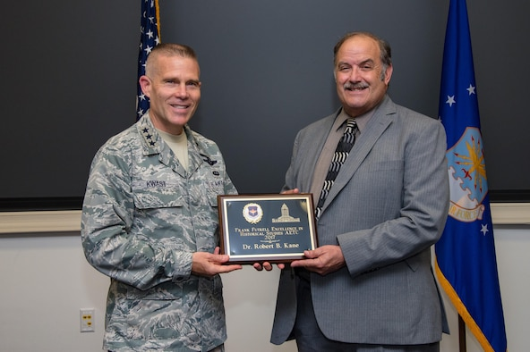 """Lt. Gen. Steven Kwast, Air University commander and president presents the 2017 Air Education and Training Command's Frank Futrell Excellence in Historical Studies award to Dr. Robert Kane, AU historian, July 14, 2017, Maxwell Air Force Base, Ala. Kane was recognized for his book titled, """"So Far from Home Royal Air Force and Free French Air Force Flight Training at Maxwell and Gunter Fields during World War II.""""(U.S. Air Force photo/ Melanie Rodgers Cox)"""