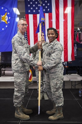 Col. Greg Buckner, 90th Maintenance Group commander, passes the guidon to Lt. Col. Stephanie Wilson, 90th Missile Maintenance Squadron commander, during the 90th MMXS assumption of command ceremony July 18, 2017, as Master Sgt. Jennifer Villela, 90th MMXS first sergeant, stands in the background on F.E. Warren Air Force Base, Wyo. The ceremony signified the transition of command from Lt. Col. Jeremy Russell to Wilson. (U.S. Air Force photo by Lan Kim)
