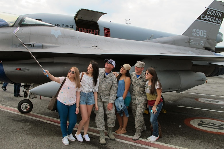 U.S. Air Force Senior Master Sgt.  Charles Bowen (left) and Staff Sgt. Matthew Parent, both assigned to the South Carolina Air National Guard's 169th Aircraft Maintenance Squadron, take a selfie with visitors to the Colombian Air Force's Feria Aeronautica Internaccional – Colombia in Rionegro,  July 15, 2017. The South Carolina Air National Guard is supporting its State Partner with providing two F-16s to the air show at Rionegro, Antioquia, Colombia from July 13-16, 2017. The United States military participation in the air show provides an opportunity to strengthen our military-to-military relationships with regional partners and provides the opportunity to meet with Colombian air force counterparts. The South Carolina National Guard has been paired with Colombia through the National Guard's State Partnership Program since 2012. (U.S. Air National Guard photo by Capt. Stephen D. Hudson).