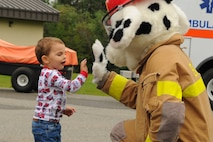 A child high-fives Sparky, the Eielson Fire Department mascot, during an open house on July 15, 2017, at Eielson Air Force Base, Alaska. Sparky greeted families as they arrived to the open house. (U.S. Air Force photo by Airman Eric M. Fisher)