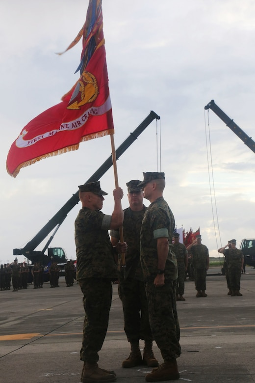 U.S. Marine Corps Brig. Gen. Thomas D. Weidley (left), the incoming 1st Marine Aircraft Wing commanding general takes the unit colors from Maj. Gen. Russell A. Sanborn (right), outgoing commanding general, representing the passing of command during a change of command ceremony at Marine Corps Air Station Futenma, Okinawa, Japan, June 29, 2017. Sanborn will assume command of Marine Forces Europe and Africa. (U.S. Marine Corps photo by Lance Cpl. Isabella Ortega)