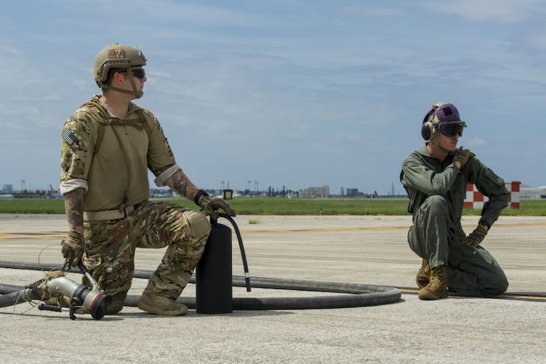 Air Force Staff Sgt. Mark Goddard and Lance Cpl. Westley W. Joints await the arrival of an F-35B Lightning II aircraft with Marine Fighter Attack Squadron 121 at Kadena Air Force Base, Okinawa, Japan, June 27, 2017. The Marines and Airmen perform hot pit refuels. Goddard is a bulk fuel specialist with 18th Logistics and Readiness Squadron, 353 Special Operations Group, 18th Wing. Joints is a bulk fuel specialist with Marine Wing Support Squadron 172, Marine Aircraft Group 36, 1st Marine Aircraft Wing, III Marine Expeditionary Force. VMFA-121 is based out of Iwakuni, Japan. The two-day exercise enabled the U.S. Air Force and Marine Corps to improve interoperability and develop tactics, techniques and procedures involving the new aircraft for future joint FARP operations throughout the Indo-Asia Pacific Theater. (U.S. Marine Corps photo by Lance Cpl. Deseree Kamm)