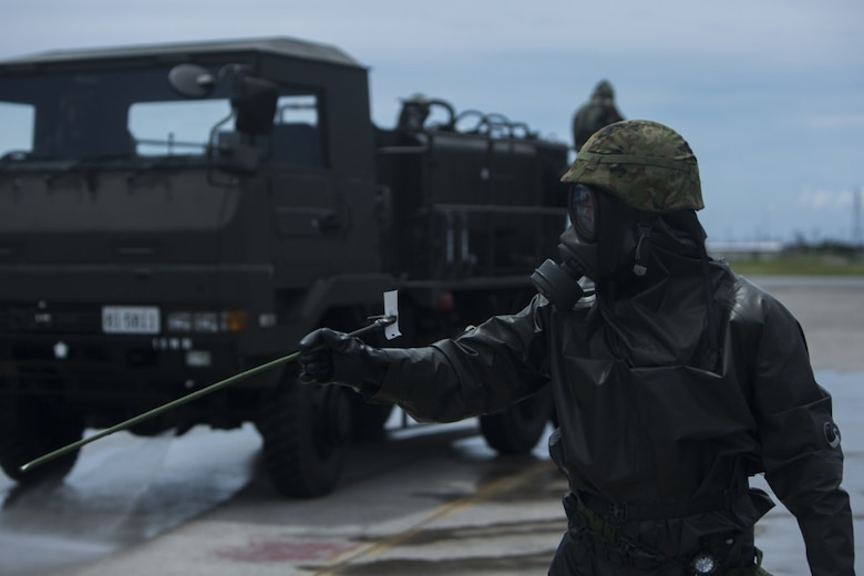 A Japanese Ground Self-Defense service member directs a decontamination truck during a simulated joint study with U.S. Marine chemical, biological, radiological and nuclear defense specialists from Marine Wing Headquarters Squadron 1 at Marine Corps Air Station Futenma, Okinawa, Japan, July 13, 2017. The joint study tests Marines' and JGSDF CBRN response capabilities. The simulated mission affords Marines and JGSDF soldiers the opportunity to show each other their capabilities and to strengthen their relationship. The JGSDF service member is with 15th Nuclear, Biological, Chemical Defense Unit (U.S. Marine Corps photo by Cpl. Kelsey Dornfeld).