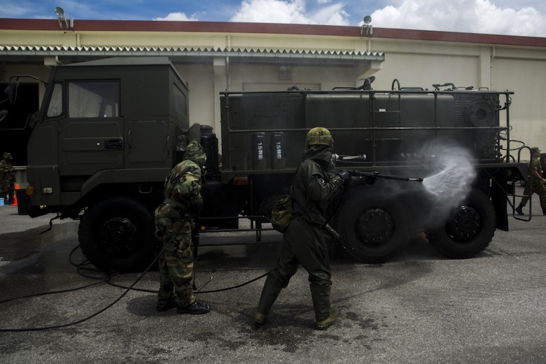 U.S. Marine Lance Cpl. Enrique Puentes Jr. sprays water on a Japanese Decontamination Truck with a Japanese Ground Self-Defense member during a simulated joint study with the JGSDF at Marine Corps Air Station Futenma on July 13, 2017. The Marines and JGSDF soldiers were integrated into one force combining U.S. and Japanese equipment while utilizing both countries' methods of decontamination. Puentes, a native of Tampa, Florida, is a CBRN defense specialist with Marine Wing Headquarters Squadron 1, and the JGSDF soldier is with 15th Nuclear, Biological, Chemical Defense Unit (U.S. Marine Corps photo by Cpl. Kelsey Dornfeld).