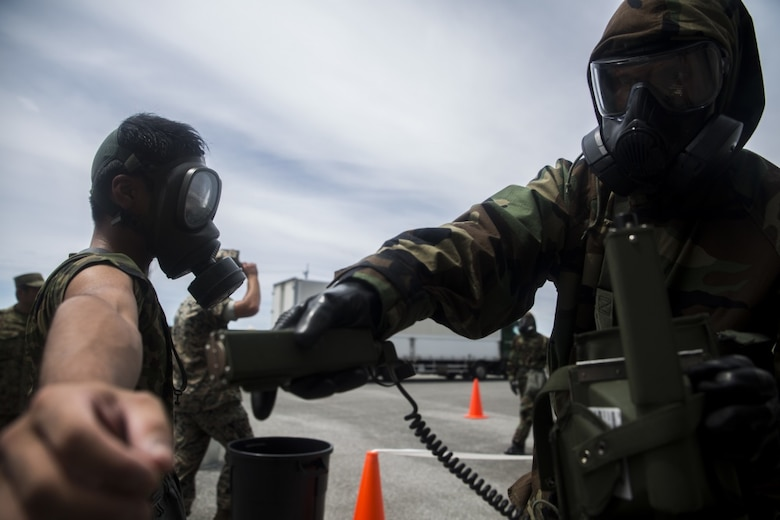 U.S. Marine Cpl. Varun Chethan scans a Japanese Ground Self-Defense member for chemicals during a simulated joint study with the JGSDF at Marine Corps Air Station Futenma on July 13, 2017. The events tests Marines' and JGSDF chemical, biological, radiological and nuclear response capabilities to a chemical attack on a flight line. This three day study allowed the service members the opportunity to share their capabilities and work together. Chethan, a native of Ann Arbor, Michigan, is a CBRN defense specialist with Marine Wing Headquarters Squadron 1, and the JGSDF service member is with 15th Nuclear, Biological, Chemical Defense Unit (U.S. Marine Corps photo by Cpl. Kelsey Dornfeld).