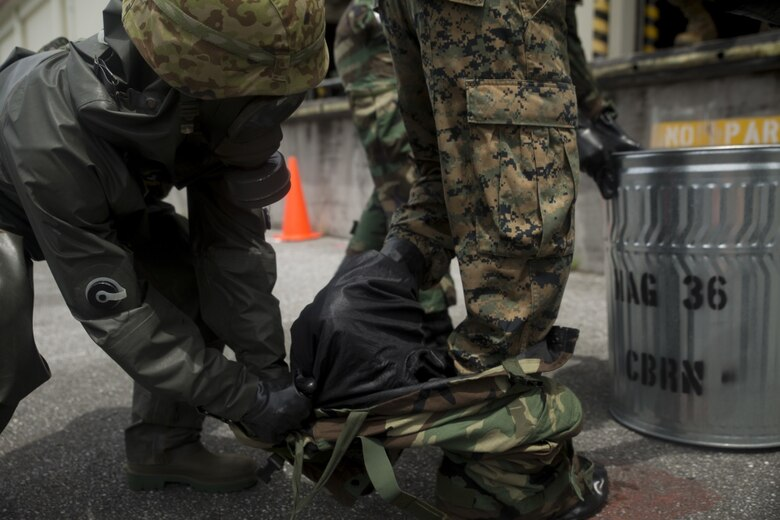A Japanese Ground Self-Defense service member helps U.S. Marine Lance Cpl. Enrique Puentes Jr. get out of his Mission Oriented Protective Posture suit during a simulated joint study at Marine Corps Air Station Futenma, Okinawa, Japan, July 13, 2017. The JGSDF service member is with 15th Nuclear, Biological, Chemical Defense Unit. Puentes, a native of Tampa, Florida, is a CBRN defense specialist with Marine Wing Headquarters Squadron 1. (U.S. Marine Corps photo by Cpl. Kelsey Dornfeld).