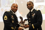 Army Capt. Eric Moton, right, chief of the Finance Division for the Army Reserve's 99th Regional Support Command, presents a retirement award to Army Sgt. 1st Class Christopher Moore during a ceremony at Joint Base McGuire-Dix-Lakehurst, N.J., Nov. 5, 2016. Moton earned his Ph.D. in business administration in 2016, joining a select group of Army Reserve soldiers who have pursued higher education. Army photo by Staff Sgt. Shawn Morris
