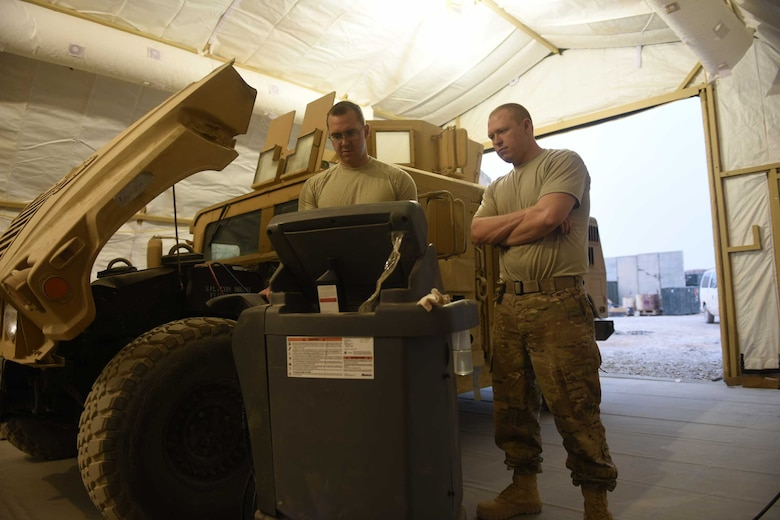 U.S. Air Force Staff Sgts. Adam Martin, a fire truck maintenance specialist, and Shawn Benton, an aerospace ground equipment craftsman, both deployed in support of Combined Joint Task Force – Operation Inherent Resolve and assigned to the 370th Air Expeditionary Advisory Group, Detachment 1, use a refrigerant recovery station to perform a leak test and charge the air conditioning system of a Humvee inside the vehicle maintenance tent at Qayyarah West Airfield, Iraq, July 2, 2017. The new vehicle maintenance facility improved efficiency for the maintainers as they can now not only get out of the sun to work on their vehicles, but also complete tasks during all hours of the day. CJTF-OIR is the global Coalition to defeat ISIS in Iraq and Syria.  (U.S. Air Force photo by Tech. Sgt. Jonathan Hehnly)