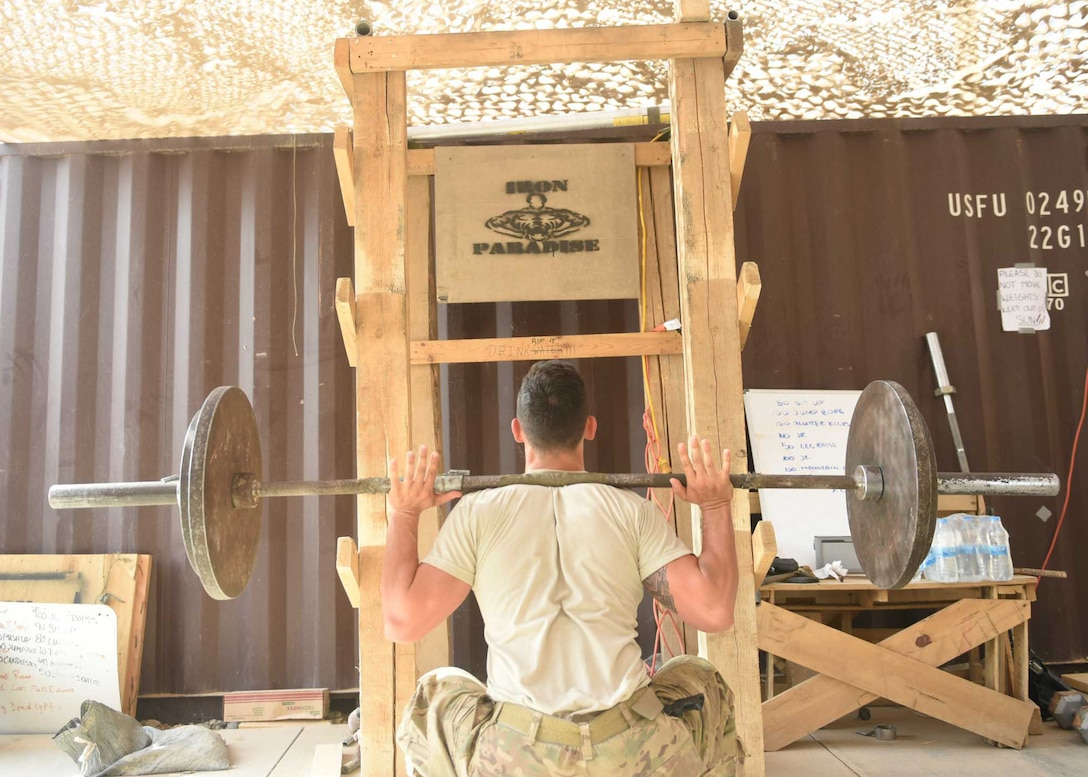 """U.S. Air Force Airman 1st Class Zachary Tilley, an expeditionary maintenance liaison specialist deployed in support of Combined Joint Task Force – Operation Inherent Resolve and assigned to the 370th Air Expeditionary Advisory Group, Detachment 1, performs a barbell squat in front of a makeshift squat rack in the 370th AEAG detachment's """"Iron Paradise"""" gym at Qayyarah West Airfield, Iraq, July 2, 2017. The air advisors built the """"Iron Paradise"""" gym, which includes a makeshift squat rack, bench press, preacher curl bench and other recently acquired weights, creating an area often filled with Air Force and Army personnel trying to maintain physical fitness in their austere location. CJTF-OIR is the global Coalition to defeat ISIS in Iraq and Syria. (U.S. Air Force photo by Tech. Sgt. Jonathan Hehnly)"""