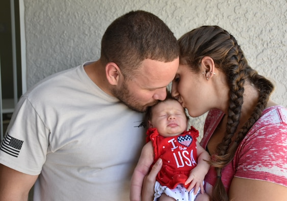 Staff Sgt. Jeff A. Parrish Jr., left, 920th Aircraft Maintenance Squadron aircraft armament systems technician, and his wife, Jacquelyne Parrish, kiss their daughter Raelynn Noelle Parrish, July 4, 2017, outside of their home in Ocoee, Florida. Jeff returned home shortly before the early birth of their first child after a four-month deployment to Afghanistan. (Courtesy photo)