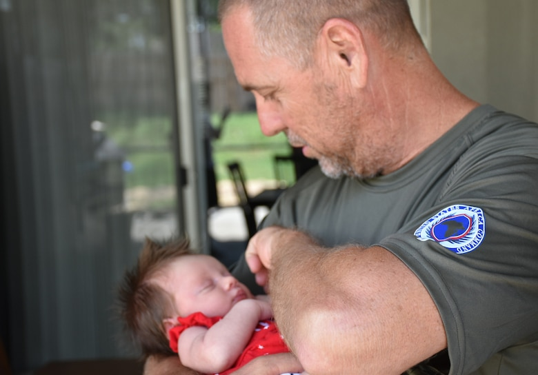Tech. Sgt. Jeff A. Parrish, 920th Maintenance Squadron munitions assistant flight chief, holds his granddaughter, Raelynn Noelle Parrish, July 4, 2017 at his son's home in Ocoee, Florida, several weeks after returning home from a four-month deployment to the Horn of Africa. (Courtesy photo)