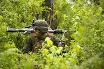 A Marine crouches to remain concealed during a Marine Combat Readiness Exercise at Camp Lejeune, N.C., June 21, 2017. The Marines conducted an airfield seizure and movement to contact drills during this MCCRE iteration to maintain unit efficiency and prepare for future operations overseas. The Marines are with 1st Battalion, 8th Marine Regiment. (U.S. Marine Corps photo by Cpl. Luke Hoogendam)