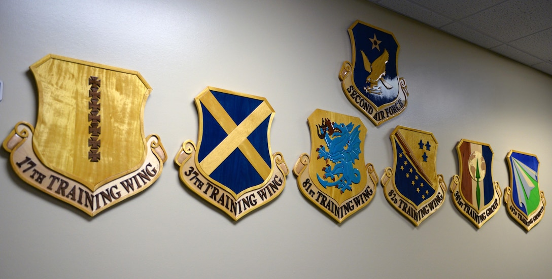 Wing shields hang on the wall at the 81st Training Support Squadron Military Training Leader School's new location in Lott Hall, July 17, 2017, on Keesler Air Force Base, Miss. The course recently moved locations from Allee Hall to Lott Hall, and now features its own dedicated classroom, CPR training room, conference room and instructor offices, as well as additional resources and career field heritage pieces. (U.S. Air Force photo by 2nd Lt. Toney Doan)
