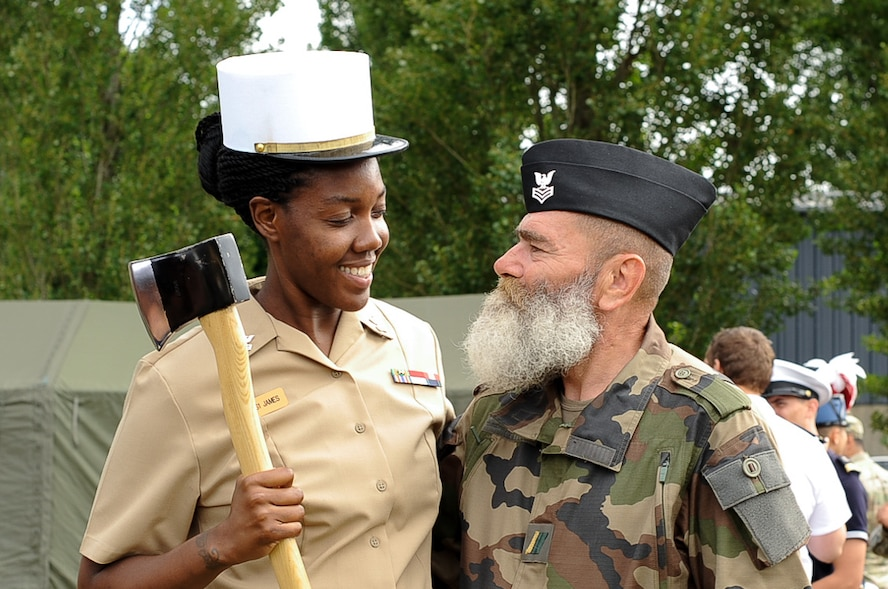A U.S. Navy Seaman and a member of the Armée de Terre switch hats for a photo at Camp de Satory, France, July 12, 2017. During rehearsals, military members from countries had the opportunity to interact and learn from the other's military traditions and culture, further strengthening the bond between old allies. (U.S. Air Force photo by Airman 1st Class Savannah L. Waters)