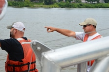 """Brian Collins and Kent Browning of the Technical Support Branch's Waterways Section, aboard the Huntington District's 26 ft. survey boat, plan their route to survey the navigation channel after the demolition of piers from the old Ironton-Russell Bridge. The bridge was demolished once it was replaced by the new Oakley Collins Memorial Bridge that opened in November 2016. Brian and Kent worked closely with the Ohio Department of Transportation and the U.S. Coast Guard's Huntington Marine Safety Unit to reopen the channel once the demolition was complete. Brian and Kent used the array of sophisticated sonar aboard the survey boat to make sure that no obstructions to navigation were present after detonation. Once they gave the """"all clear"""" to the Coast Guard the channel was once again open for commercial traffic."""