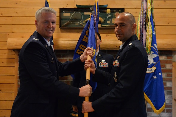 Col. William Angerman, 50th Network Operations Group commander, hands the 23rd Space Operations Squadron guidon to the squadron's new commander, Lt. Col. Kenneth Holmes, during the unit's change of command ceremony at New Boston Air Force Station, New Hampshire, July 11, 2017. Holmes was preceded by Lt. Col. Marty Easter. (Courtesy photo)