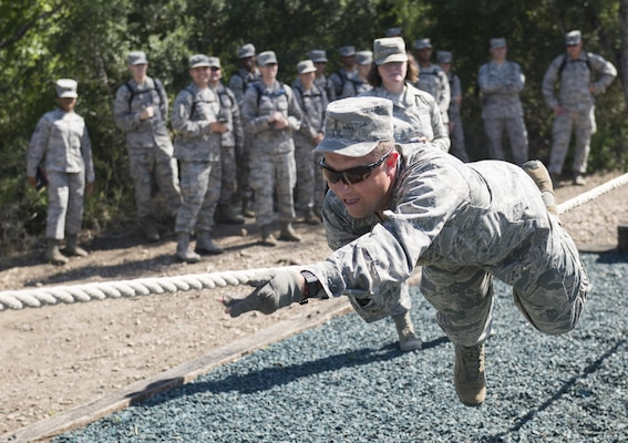 A chaplain candidate attempts to complete one of the  Creating Leader Airmen Warriors, or CLAW, course's obstacles during a tour of the Basic Expeditionary Airmen Skills Training at Joint Base San Antonio-Lackland, Texas, July 5, 2017. The tour was part of the Chaplain Candidate Intensive Internship. (U.S. Air Force photo by Senior Airman Krystal Wright)